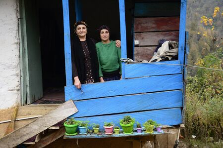 Lasak, IRAN - November 22, 2018 close up portrait of two elderly woman in front of balcony. Gilan Province