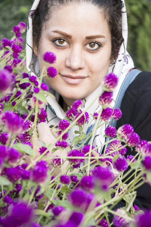 A portrait of a young beautiful muslim woman in a white shawl in front of purple flowers, vertical shot