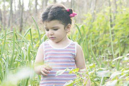 Close-up portrait of alone girl at garden, green field at spring season 版權商用圖片