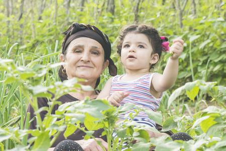 Senor Grandmother portrait with her grandchild at garden enjoying together