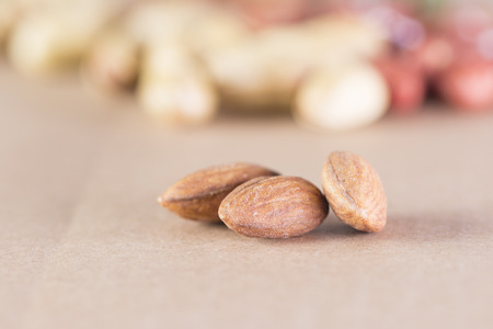 Close-Up of dry seeds over background, dry almond kernels at front