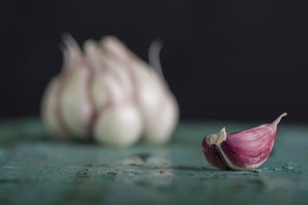 Fresh garlic bulbs on turquoise wooden kitchen table, healthy everyday eathing background Фото со стока