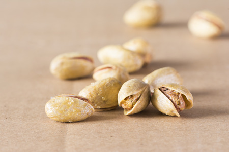 Salted pistachio nuts on light brown background Фото со стока