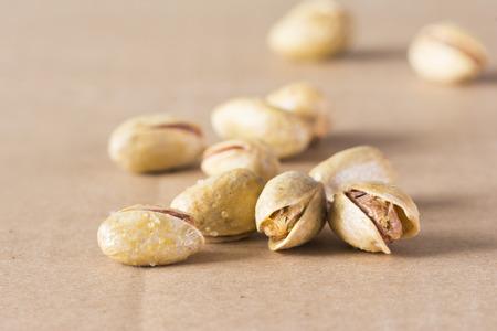 Salted pistachio nuts on light brown background Reklamní fotografie