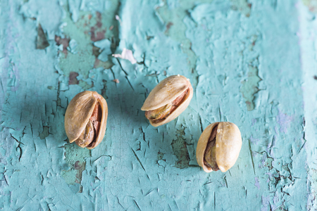 Three pistachios on turquoise wooden plank, top view point Imagens