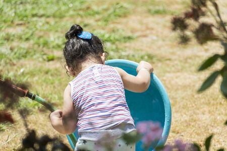 Backside of little girl playing with hose and blue plastic tub at backyard