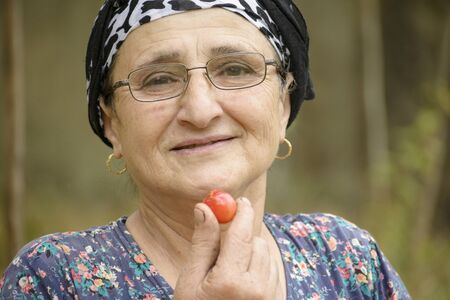 Happy senior woman eating red plum, healthy eating concept
