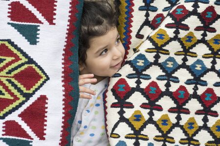 Little girl close up portrait in kilims with traditional folk geometric patterns