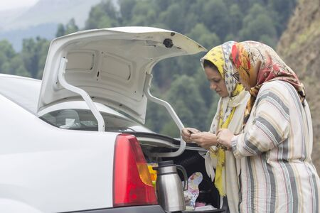 Gilan Province- North of IRAN-August 7, 2019-two Muslim woman making tea at backside of car