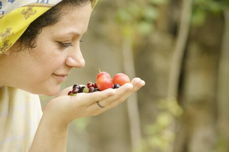 Young woman smelling ripen spring time plums odor in hand, healthy eating concept