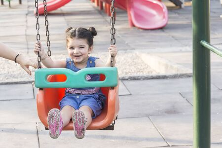 Happy laughing little girl enjoying on swing in playground, mothers hand support her at motion