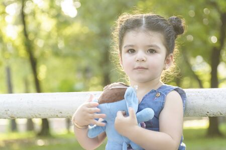 Close up Little girl portrait holding a blue elephant doll at hands in outdoor area, childhood memories concept