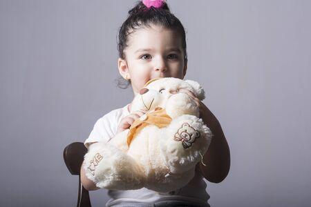 Close up of Little girl portrait holding a teddy bear doll in hands seated on chair, childhood memories concept