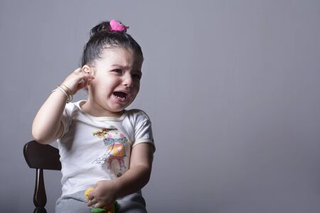 Lonely girl crying in front of gray background, pain or parent argument fear concept