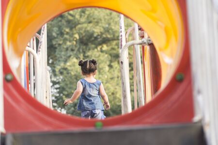 Backside of a little girl having fun in playground area, children leisure activity equipment  Imagens