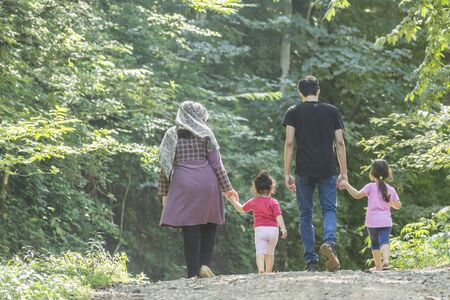 Backside of young family walking together outside in green nature, travel and spending holiday time concept