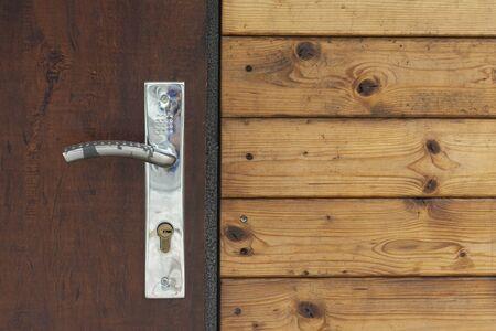 Door shot detail, metallic handle with wooden planks in building  Imagens