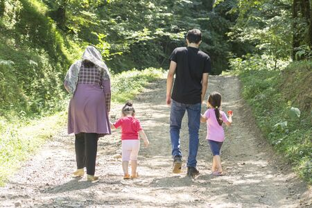Young family walking in rural road together outside in green nature, travel and spending holiday time concept