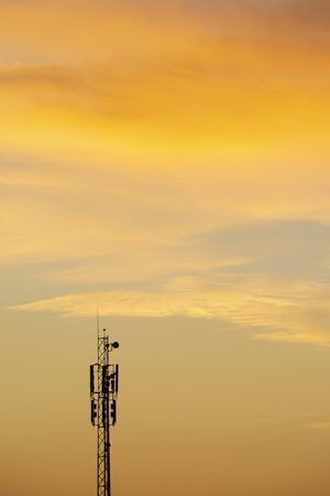 Communication antenna tower at dawn time with beautiful clouds at sky, vertical shot