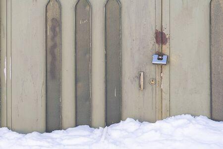 old rusty door fasten by steel padlock, winter snow stacked in front of door