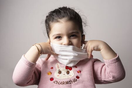 Little girl removing hospital mask from her face, coronavirus outbreak and air pollution concept