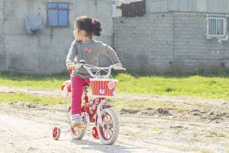 Little girl riding a red four-wheels bicycle in dirt road looking behind, escaping by bicycle