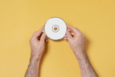Male hands holding a CD-DVD in front of yellow background, editable mock up template for your design, label selection path included Фото со стока