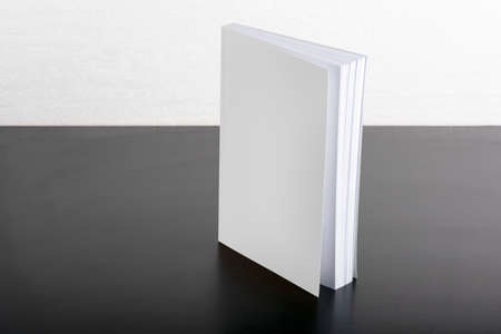 Book with blank cover on black background, editable mock up template ready for your design, selection path included.