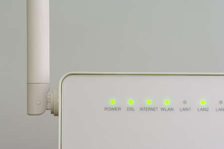 White wireless internet router with antenna isolated on gray background Stock Photo