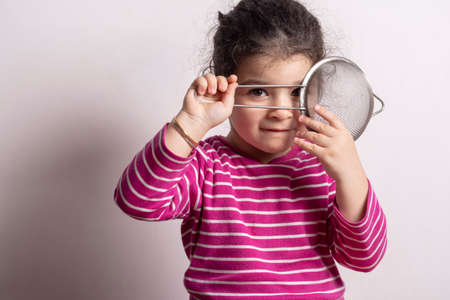 Little girl with a strainer in front of her face looking to the camera, childhood memories cooking experience