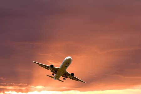 Een vliegtuig dat in de oranje hemel vliegt Stockfoto