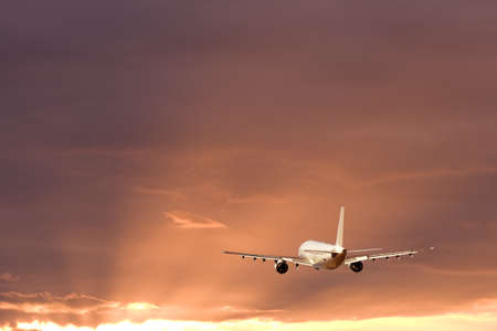 An airplane flying in the orange sky photo