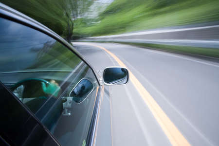 The car moves at great speed at the sunny day.