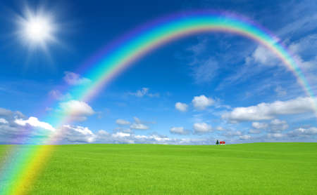 Green grass and red roof house and rainbow