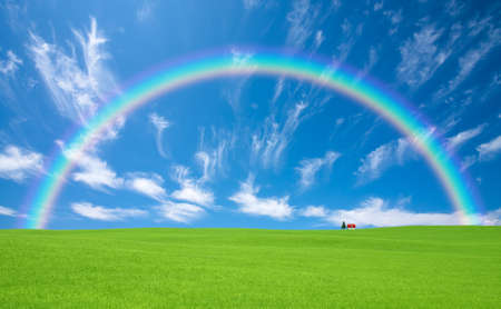 Green grass and red roof house and rainbow   photo