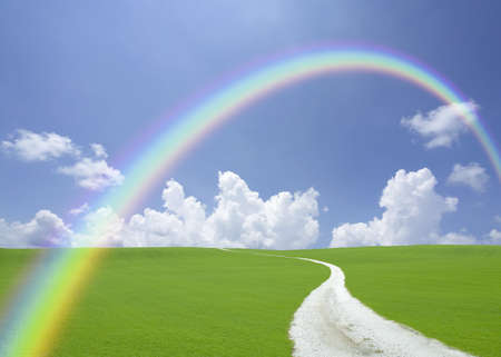 rainbow scene: Green hill and white road with rainbow Stock Photo