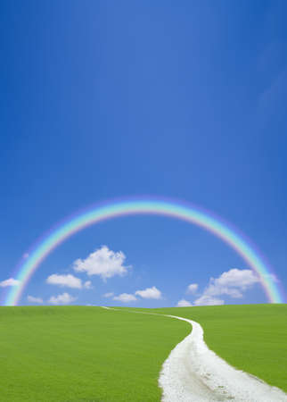 Green hill and white road with rainbow photo