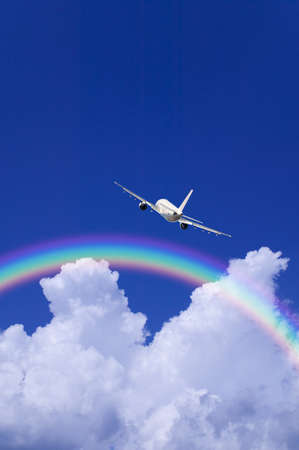jetliner: A jetliner aeroplane flying over white clouds towards a rainbow in blue sky Stock Photo