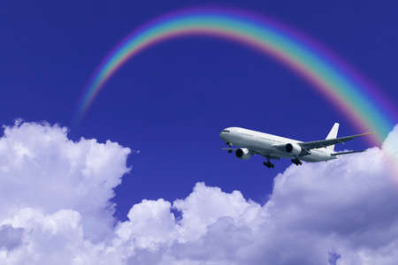 cloud formation: A jetliner aeroplane flying over white clouds towards a rainbow in blue sky Stock Photo