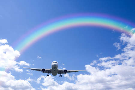 arc: A jetliner aeroplane flying over white clouds and rainbow in blue sky