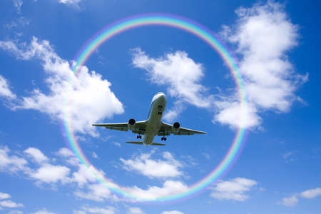 A jetliner aeroplane flying over white clouds and rainbow in blue sky photo