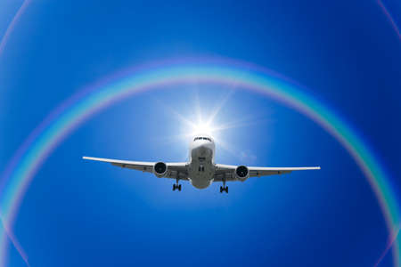 cloud formation: A jetliner aeroplane flying with rainbow in blue sky Stock Photo