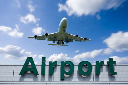 A jetliner aeroplane flying over Airport sign towards Stock Photo