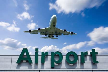 A jetliner aeroplane flying over Airport sign towards Foto de archivo