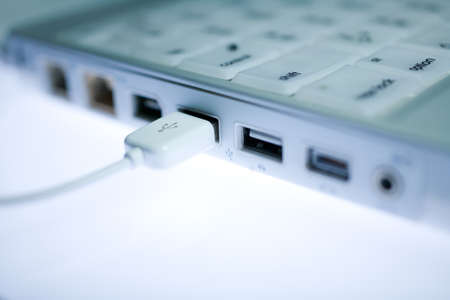 USB port on the side of a laptop with an external peripheral device attached photo