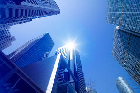Looking up at tall skyscrapers against a blue sky in an urban environment