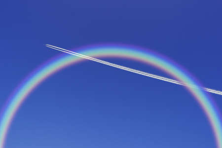 A jetliner aeroplane flying with rainbow in blue sky photo