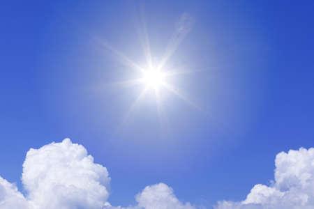 A bright white sun shining above white fluffy cumulus clouds in a blue sky