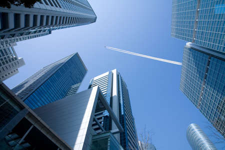 A view up through tall skyscrapers to a patch of blue sky with a jetliner flying overhead.