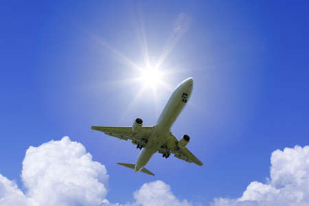 jetliner: A jetliner aeroplane flying over white clouds and sun Stock Photo
